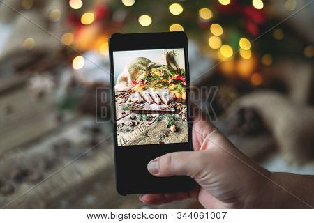 Female Hands Take A Photo Of Traditional German Bread Stollen On A Wooden Table With Bokeh Lights.