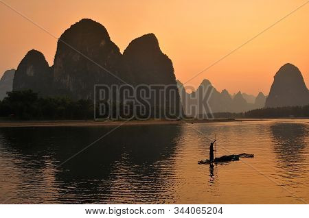 Silhouette Of Fishermen In Yangshuo, Sunset At The Li River. Yangshuo Is A Popular Tourist County An