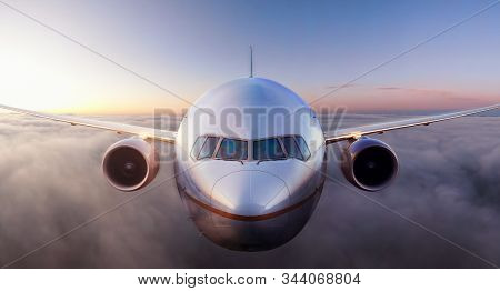 Airplane Flying Above The Clouds During Colorful Sunset Or Sunrise. Concept Of Travel, Transportatio