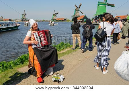 Zaanse Schans, Netherlands - 22 April 2019: Woman in traditional dress playing accordion among tourists sightseeng famous Dutch windmills in Zaanse Schans, is a typical small village within Amsterdam