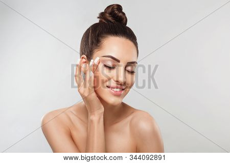Beautiful Smiling Woman With Healthy Smooth Facial Clean Skin Applying Cosmetic Cream And Touch Own