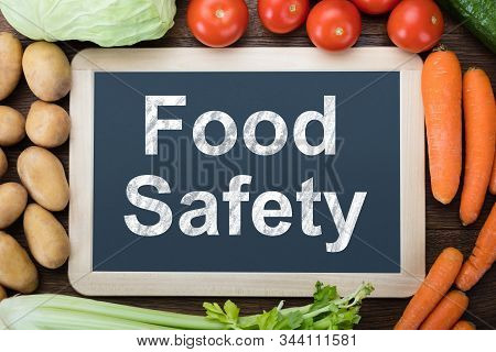 Elevated View Of Juicy Fresh Vegetables Around Food Safety Text On Slate Board Over Counter