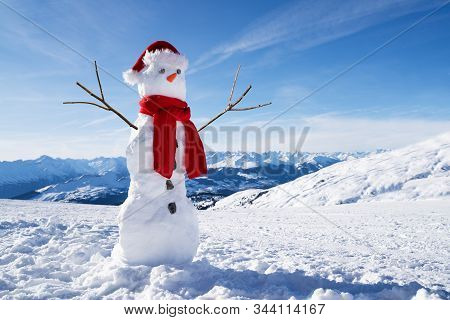 Low Angle View Of An Incomplete Snowman With Hat And Scarf On Snowy Field