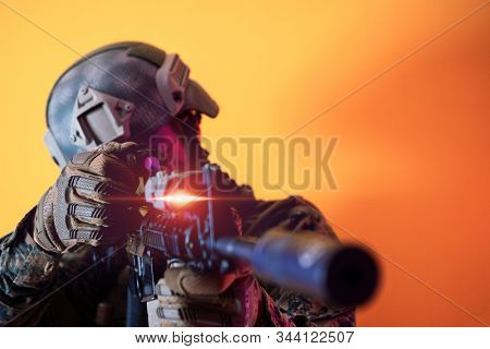modern warfare american marines soldier in action while sneaking aiming  on laseer sight optics  in combat position and  searching for target in battle yellow background