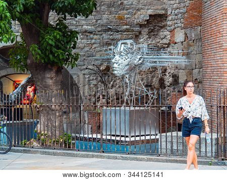 Barcelona, Spain - August 2019: Silver Art Installation Near The Old Brickwall, Medium Shot. Young F
