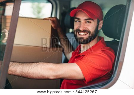 Image of happy young delivery man in red uniform smiling and driving van with parcel boxes