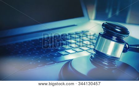 Cyber crime concept image, gavel on laptop computer.
