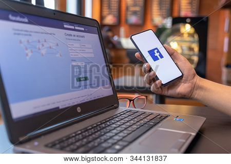 Chiang Mai, Thailand - May 01,2019: Man Holding Xiaomi Mi Mix3 With Facebook App On The Screen With