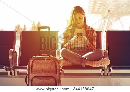 Air Travel Concept With Young Casual Girl Sitting With Hand Luggage Suitcase. Airport Woman On Smart