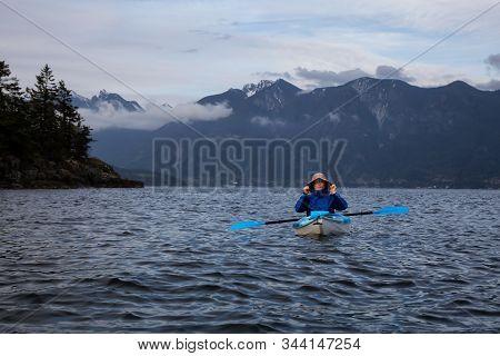 Adventurous Man On A Kayak Is Paddling In Howe Sound During A Cloudy Evening. Taken Near Bowen Islan