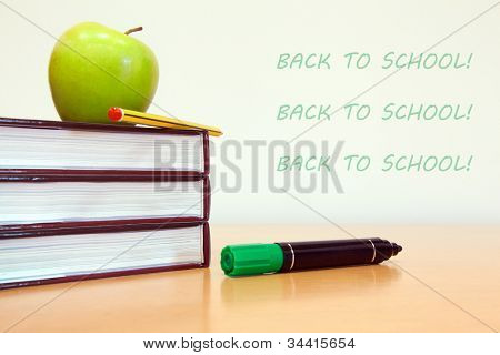 School books with apple on desk at modern classroom