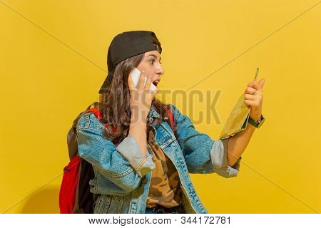 Talking On Phone, Emotions. Portrait Of A Cheerful Young Caucasian Tourist Girl With Bag In Jeans Cl