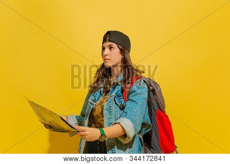Looking Forward With Map. Portrait Of A Cheerful Young Caucasian Tourist Girl With Bag In Jeans Clot