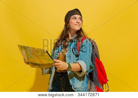 Looking At Side, Dreamful. Portrait Of A Cheerful Young Caucasian Tourist Girl With Bag In Jeans Clo