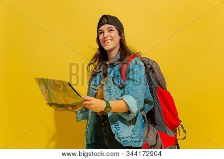 Looks Happy, Smiling. Portrait Of A Cheerful Young Caucasian Tourist Girl With Bag In Jeans Clothes