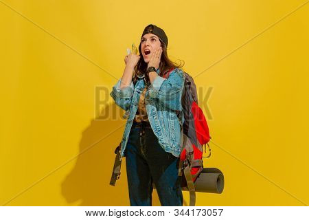 Astonished, Looking Up. Portrait Of A Cheerful Young Caucasian Tourist Girl With Bag In Jeans Clothe