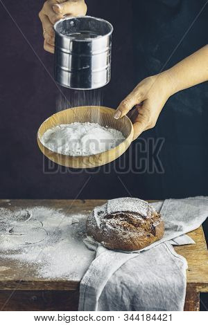 Woman Sifting Flour Through A Sieve On Wooden Table. The Chef In Dark Apron Sifts The Flour Through