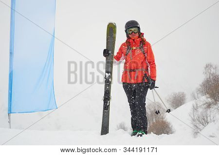 Freerider Woman Skier With Fat/wide All Mountain Skis Posing Next To A Blank Blue Flag, During A Whi