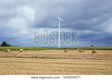 Straw Bales On A Field And Wind Turbine In Czaple, Small Village In Masovia Region Of Poland