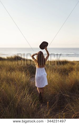 Blissful Woman Relaxing And Feeling The Breeze On Summer Sunset At The Beach. Freedom And Relax Conc