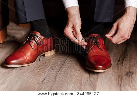 Groom Tied The Laces On The Shoes Close Up. Business Man Is Hanging Shoes Indoor In Hotel Room. Mans