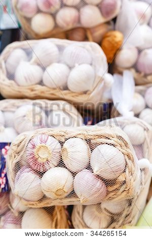 Fresh Raw Organic Garlic In Baskets As A Background. Young Garlic For Sale At Farmers Market Or Shop
