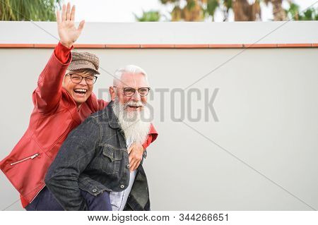 Retired Couple Playing To Be Young. Elderly Couple Having Fun. Best Elderly Friends Laughing At The