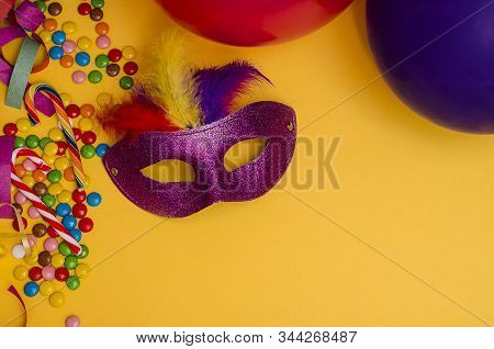 Carnival. Festive Background With Copy Space. Carnival Mask Purple With Feathers On A Yellow Backgro