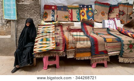 Shiraz, Iran - May 2019: Iranian Woman Selling Kilim And Carpets In Her Stall In Grand Bazaar Of Shi