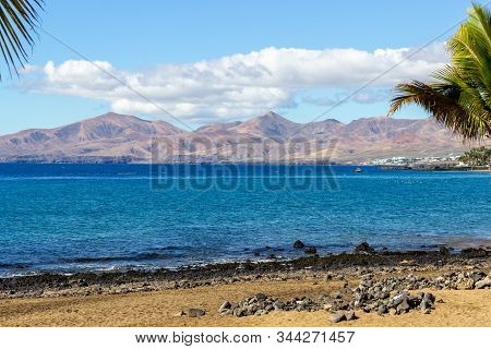 Coast Of Puerto Del Carmen At Canary Island Lanzarote With Lava Rocks, Sand, Palm Trees And Blue Wat