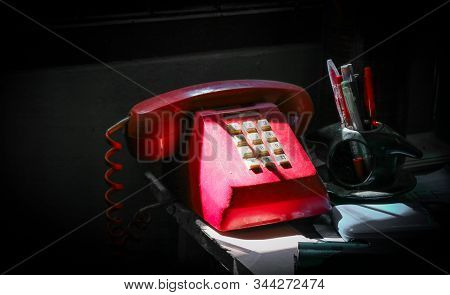 Red Oldie Telephone And Pens With Sunlight And Shadow, On The Desk.