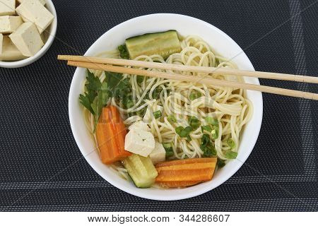 Traditional Asian Soup With Tofu Cheese, Noodles, Carrots And Zucchini On Dark Background, This Dish