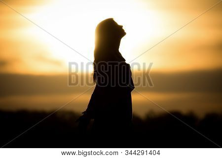 Youth Woman Soul At Orange Sun Meditation Awaiting Future Times. Silhouette In Front Of Sunset Or Su