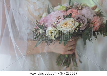 Wedding Bouquet Under The Veil. The Bride Is Holding A Bouquet. Elegant Wedding Bouquet Of Peonies.