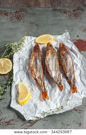Smoked Capelin And Smelt On White Paper Close-up With Lemon And Fragrant Herbs