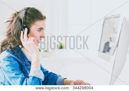 Happy Charming Young Woman Sitting And Working With Laptop Using Headset In Office