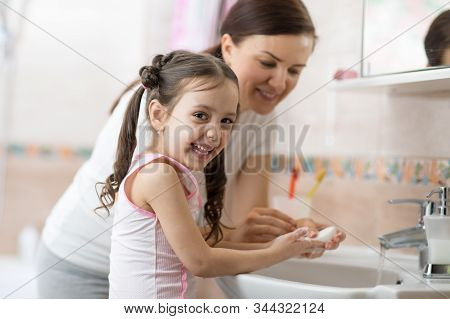 Woman And Her Daughter Child Washing Hands With Soap In Bathroom