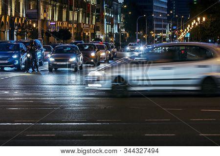 Car Traffic At Night On The Street. Illuminated Cityscape Night View