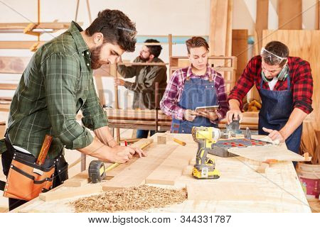 Apprentices in the tradesman training in woodworking at the workbench