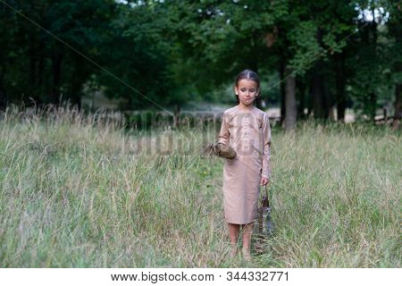 Pretty little girl with long pigtails and beautiful dirty face stands at summer meadow and holding vintage paraffin stove and flask. Orphan, child of war, poverty, hunger, famine, poor destitute kid.