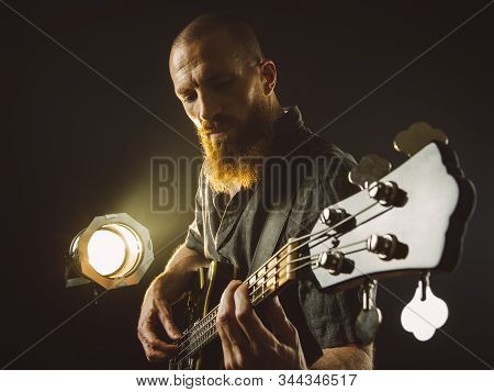 Photo Of A Bearded Man Playing Bass Guitar On Stage In Front Of Spotlights.