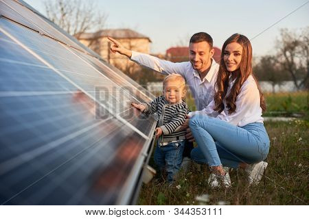 A Young Family Of Three Is Crouching Near A Photovoltaic Solar Panel, Smiling And Looking At The Cam
