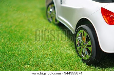Children Electric Car On A Green Artificial Grass. Copy Space.