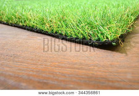 Artificial Grass Lie On The Wooden Background