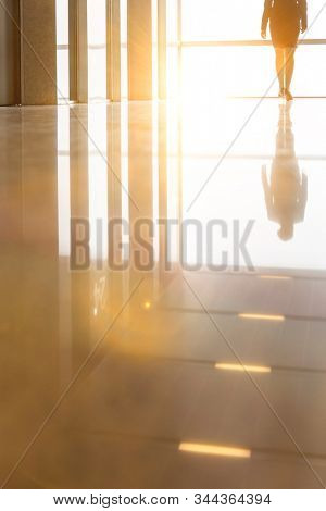 Businesswoman walking in office hall with yellow lens flare