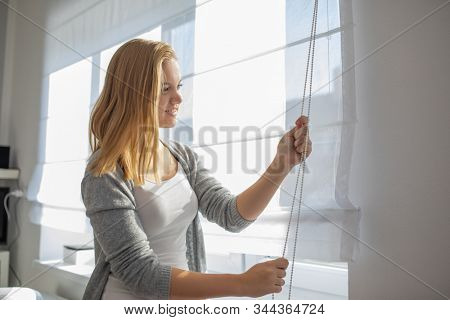 Pretty, young woman lowering the interior shades/blinds in her modern interior apartment