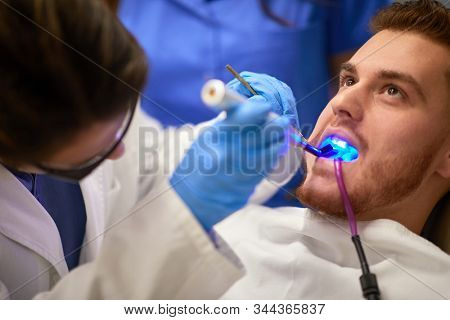 Gingerish guy at dental office having his teeth done