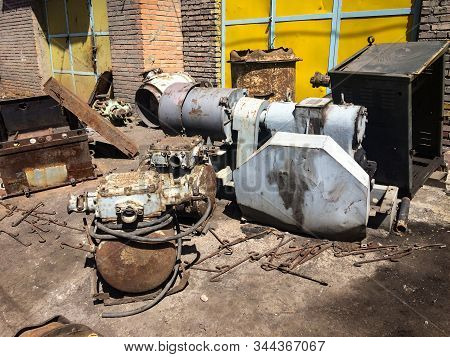 Corroded And Rusted Iron. Damaged Factory. Unused Equipment On The Ground.