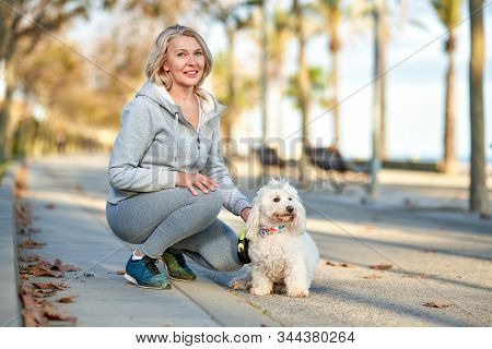 Elderly Woman Walking With A Dog Outdoors.