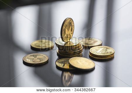 Stack Of Golden Monero Bitcoin Coin With A Lot Of Bitcoins Coins On A Table. Virtual Cryptocurrency